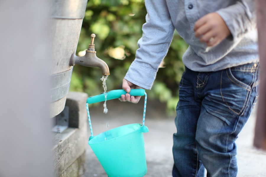 hands of a little boy filing water in bucket from rainwater barrel's tap. kid, playing, water, fill.
